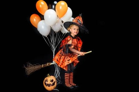 Little witch with broom and balloons
