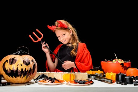 Child with halloween decorations and sweets