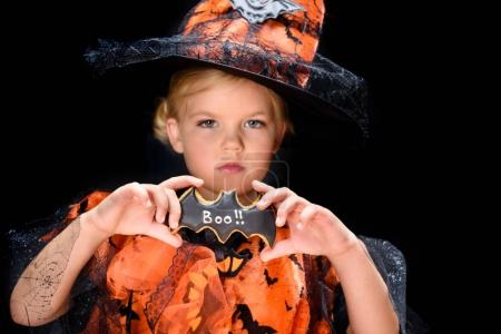 child with halloween bat cookie