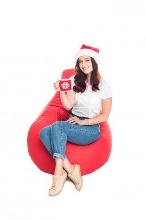 Photo for Happy woman in Santa hat with cup of coffee sitting in red bean bag chair, isolated on white - Royalty Free Image