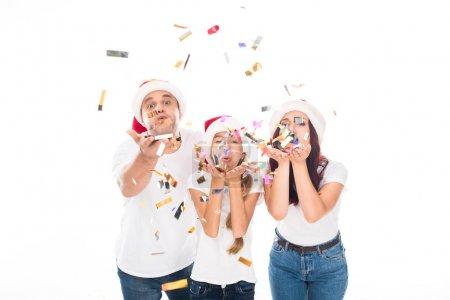 Photo pour Bonne famille dans Santa chapeaux soufflant confettis, isolé sur blanc - image libre de droit