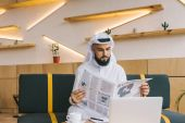muslim businessman reading newspaper