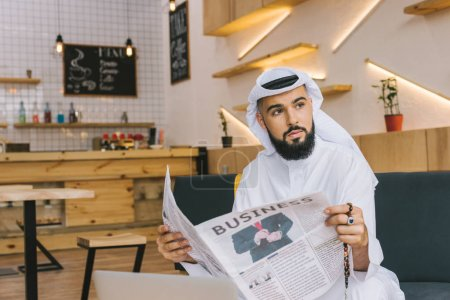 Muslim businessman with newspaper