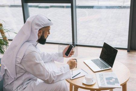 Photo pour Jeune homme d'affaires musulman, à l'aide de smartphone tout en étant assis sur le canapé avec ordinateur portable sur la table - image libre de droit