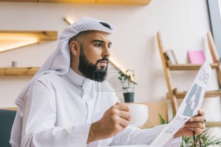 Photo pour Homme musulman lire journaux et boire du café - image libre de droit
