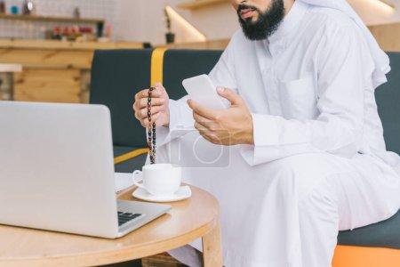 Photo pour Recadrée tir d'homme musulman travaillant avec smartphone et ordinateur portable au café - image libre de droit