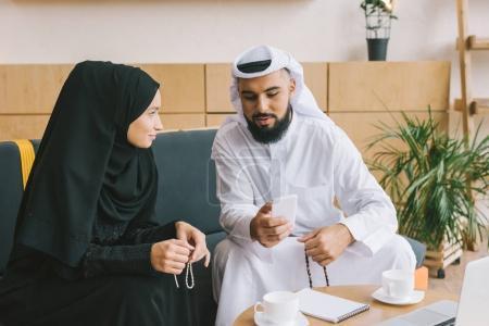 Photo pour Bel homme musulman montrant smartphone à la femme - image libre de droit