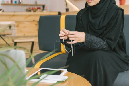 Photo for Cropped shot of muslim woman with prayer beads in cafe - Royalty Free Image
