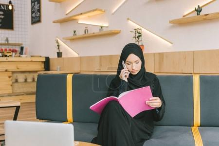 muslim woman reading magazine in cafe