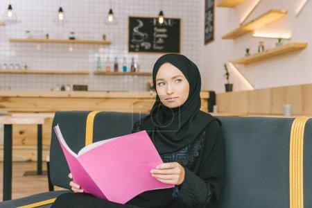 Photo pour Belle musulmane femme lecture magazine dans café - image libre de droit