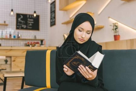 Photo pour Belle femme musulmane concentrée lisant le coran dans le café - image libre de droit