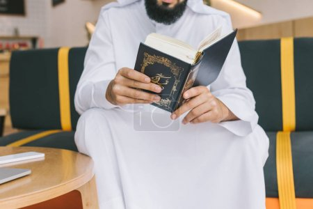 Photo pour Plan recadré d'un homme musulman lisant un coran dans un café - image libre de droit