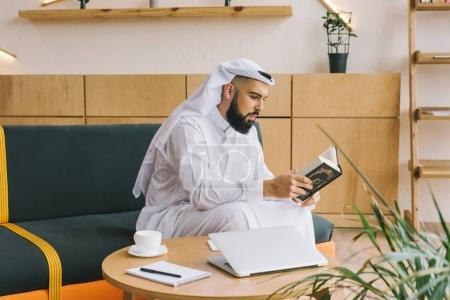 Photo for Concentrated muslim man reading quran in modern office - Royalty Free Image