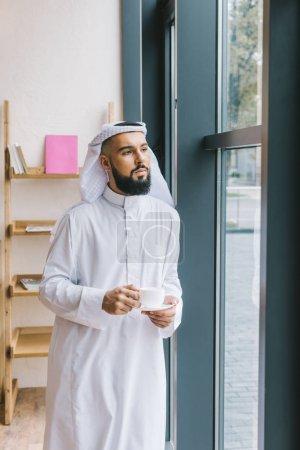 Photo pour Bel homme musulman avec une tasse de café au bureau - image libre de droit
