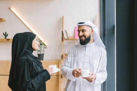 Photo pour Heureux couple musulman boire du café dans un café moderne - image libre de droit