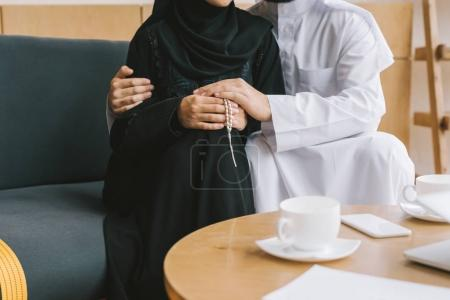 Muslim couple embracing on cozy sofa