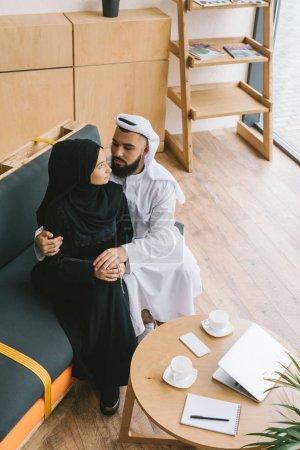 Photo pour Beau couple musulman embrassant sur le canapé dans un café moderne - image libre de droit