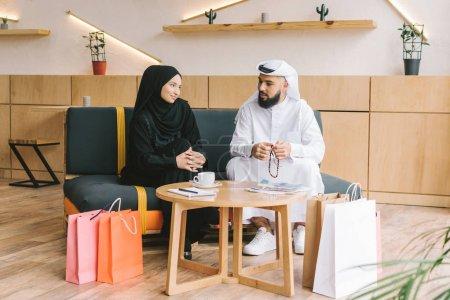 Photo pour Couple musulman assis sur le canapé dans le café après les achats - image libre de droit