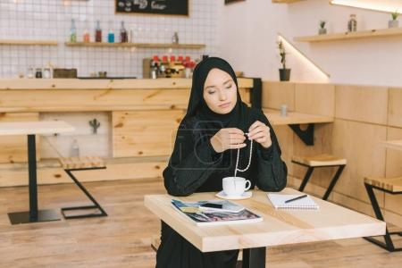 Muslim woman sitting in cafe