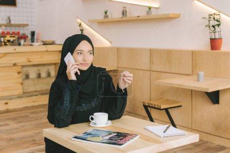 Photo pour Femme musulmane, parlant par téléphone au café avec le magazine sur la table - image libre de droit