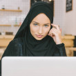 Young muslim woman using laptop in cafe and lookin...