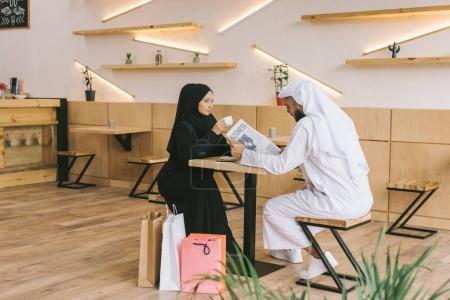 Photo pour Jeune couple musulman passer du temps dans le café après les achats - image libre de droit