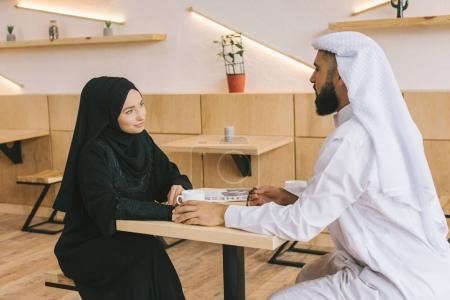 Photo pour Beau couple musulman ayant rendez-vous dans un café moderne - image libre de droit