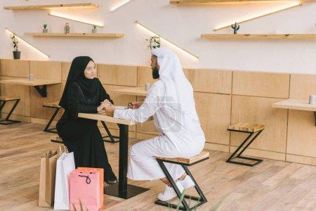 Photo pour Beau couple musulman passer du temps dans le café après le shopping - image libre de droit