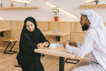 Photo for Young unhappy muslim couple having argument in cafe - Royalty Free Image