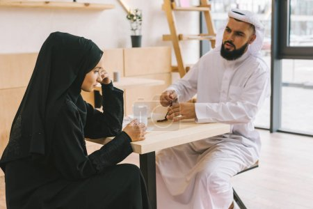 muslim couple having argument in cafe