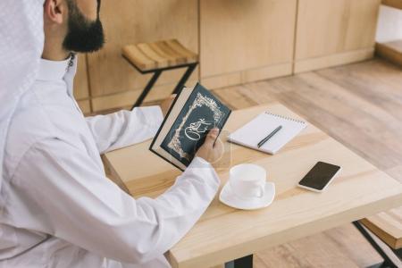 Photo pour Recadrée tir d'homme musulman avec le Coran dans café - image libre de droit