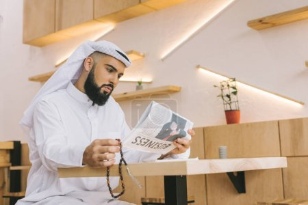 muslim man reading newspaper