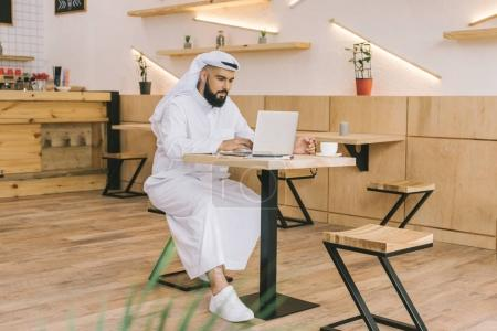 Photo for Handsome muslim man using laptop in cafe - Royalty Free Image