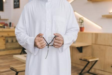 Photo pour Recadrée tir d'homme musulman avec perles de prière - image libre de droit