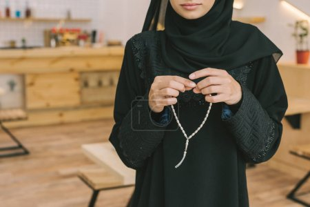 Photo for Cropped shot of young muslim woman with prayer beads in cafe - Royalty Free Image