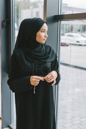 muslim woman looking at window