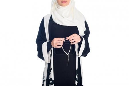 Photo pour Photo recadrée de jeune femme musulmane avec des perles de prière isolé sur blanc - image libre de droit
