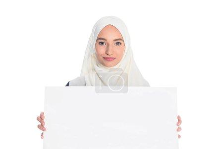 Photo pour Heureuse jeune femme musulmane tenant Conseil blanc isolé sur blanc - image libre de droit