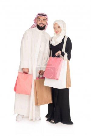 Photo pour Couple musulman avec sacs à provisions isolés sur blanc - image libre de droit