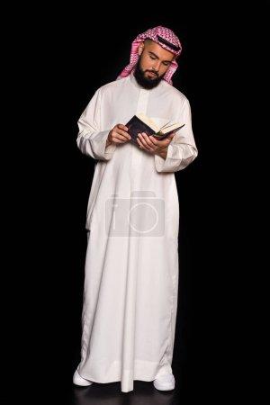 Photo pour Bel homme musulman lecture corran isolé sur noir - image libre de droit