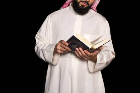 Photo for Cropped shot of muslim man reading quran isolated on black - Royalty Free Image