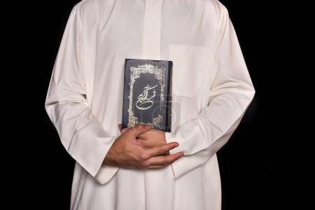 Photo pour Recadrée tir d'homme en vêtements musulmans détenant Coran isolée sur fond noir - image libre de droit