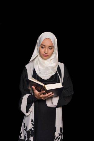 Photo pour Musulmane femme dans hijab lecture corran isolé sur noir - image libre de droit