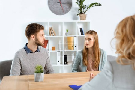 Photo for Cropped shot of psychologist and serious young couple looking at each other during psychotherapy - Royalty Free Image
