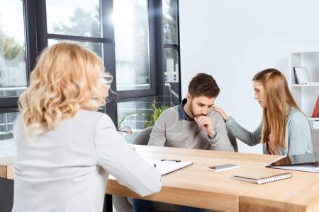 Photo pour Jeune femme soutenant bouleversé copain tout en visitant psychologue ensemble - image libre de droit