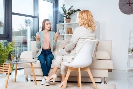 Photo for Emotional young woman talking with psychologist at therapy - Royalty Free Image