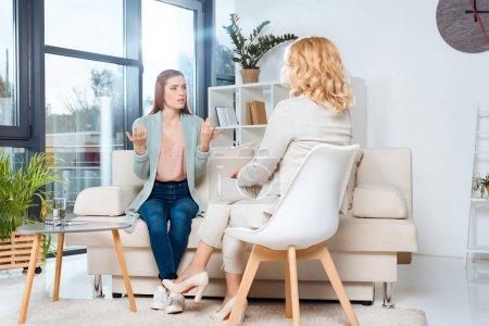 Photo pour Jeune femme émotionnelle parlant avec psychologue à la thérapie - image libre de droit