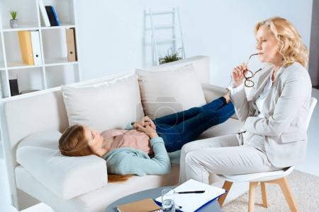 Photo pour Psychologue d'âge moyen tenant des lunettes et regardant jeune patiente couchée sur le canapé - image libre de droit