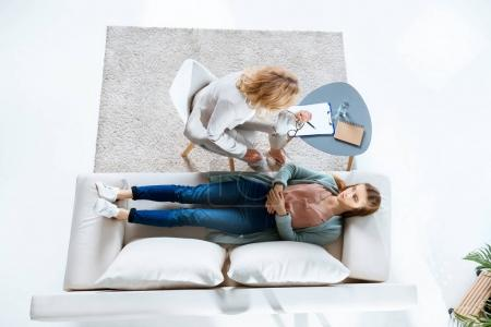 Photo for Top view of psychologist writing on clipboard while young female patient lying on couch - Royalty Free Image