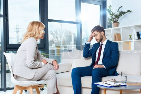 Photo for Psychologist talking with depressed young patient at psychotherapy - Royalty Free Image